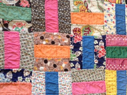Detail of Basketweave quilt showing a collection of fabrics both plains and patterned.
